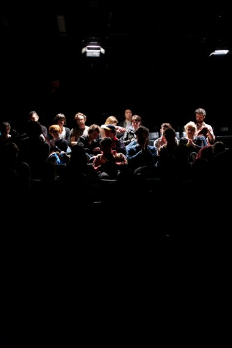 A long shot of some of the audience as they are slightly illuminated