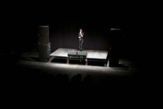 A long shot of Junko in sunglasses and dark clothes on a stage singing