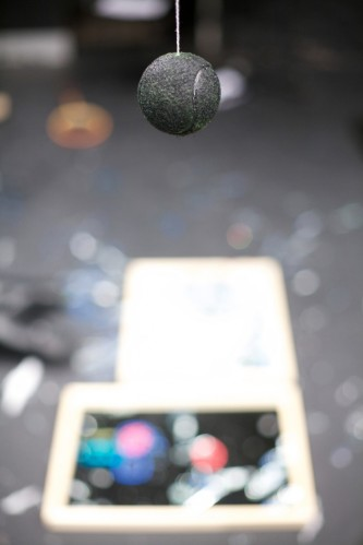 A shot of a black hanging ball, broken mirrors in the background