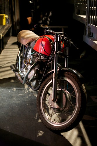 A red vintage motorcycle backstage, used as part of the performance