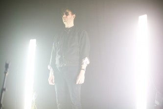 A despondent looking Mattin stands on his stage, lights at either side