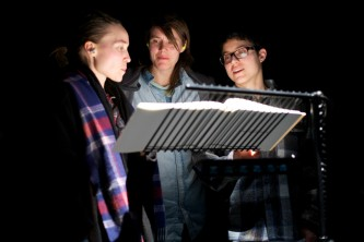 Three audience members interact as they look at a book on a music stand