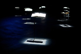Spotlit music stands hold large books, several are visible