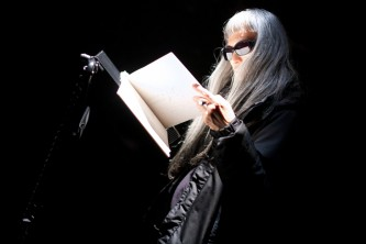 Keiji Haino, in shades reads a book on a music stand