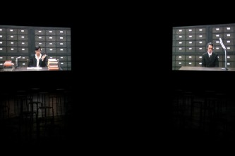 Two screens with video of two characters are hung in a dark space
