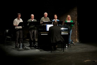 Five choir members sing stage right next to an upright piano