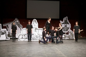 The stage has large paper figures, the ensemble cast help someone to climb