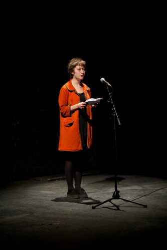A cast member in an orange coat addresses the audience