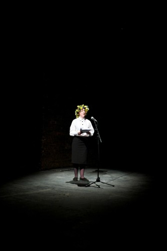 A spotlit female character in a floral headdress addresses the audience