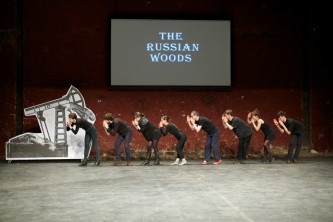 An ensemble of cast bend over in a line, all dressed in black