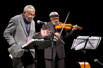 Amiri Baraka reads poetry at a microphone and Henry Grimes plays a violin