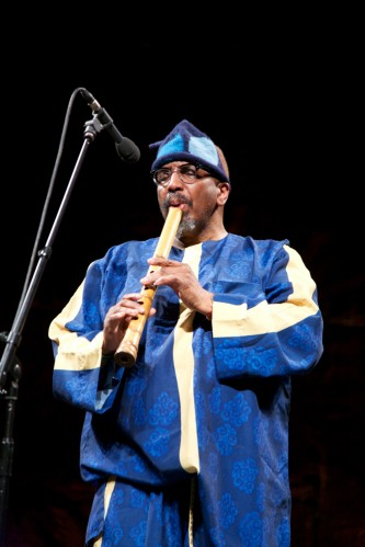 William Parker dressed in blue plays a bamboo flute