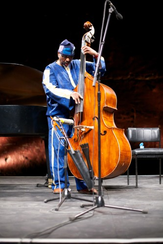 William Parker dressed in blue plays his double bass in a performance space