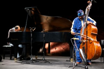 Daniel Carter plays the piano to the left and William Parker bows the bass