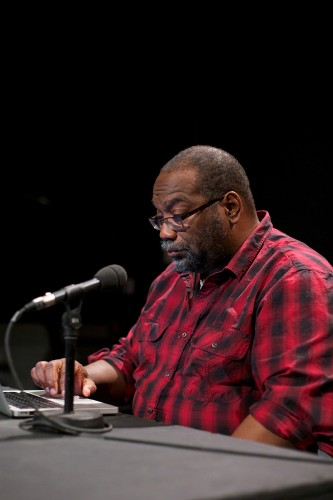 Fred Moten prepares for the talk he wears a red and black check shirt