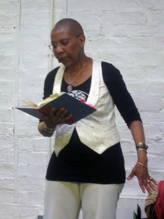 M. NourbSe Philips holds a book and reads a poem by a white brick wall