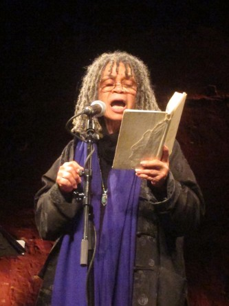 Sonia Sanchez gesticulates as she reads poetry with an open mouth