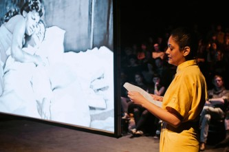 Teresa Maria Diaz Nerio in a yellow jumpsuit reads whist a B&W film plays