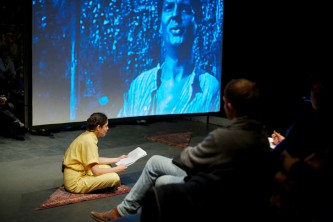 Teresa Maria Diaz Nerio in a yellow jumpsuit reads aloud whist a B&W film plays