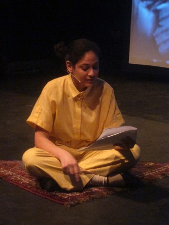 Teresa Maria Diaz Nerio in a yellow jumpsuit reads aloud whist crossed legged