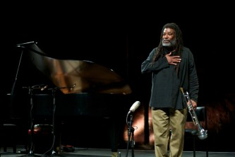 Wadada Leo Smith thanks the audience, hand on his heart, trumpet by his side