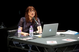 Ann Cvetkovich gesticulates as she talks in front of a laptop