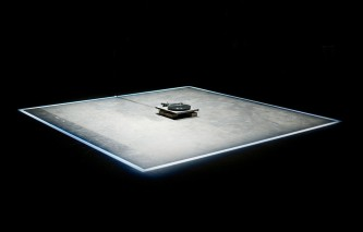 A square of light is on the floor in a dark theatre, a turntable in the centre