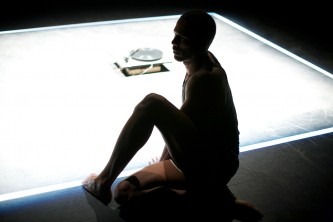 Jimmy Roberts sits at the edge of a lit square on the floor, one leg bent up