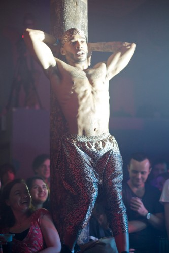 Pony Zion arms raised uses a column in the club as a prop to push against