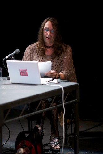 Terre Thaemlitz talks whilst sat at a table and holding papers