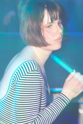 A dancer at the club with a striped top and great orange eye make up