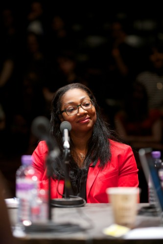 Eboni Marshall Turman wearing a red jacket sits and smiles during the talk