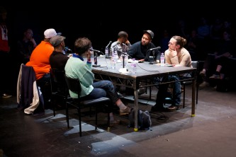The panel members at a rectangular table listen to a question
