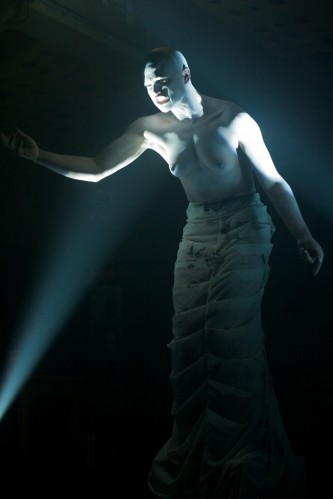 boychild dramatically lit with white lights in a white costume performs