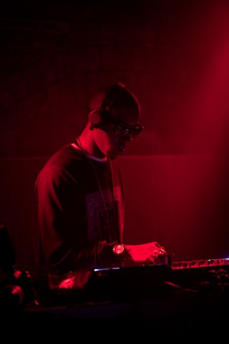 Bathed in red light MikeQ, wearing shades, DJ's at a mixer