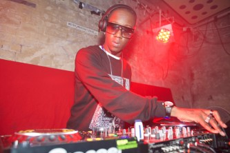 MikeQ in red and flash light, wearing shades, DJ's at a mixer