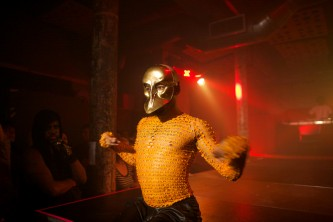 Pony Zion Garcon bathed in gold light walks down a runway in a gold mask