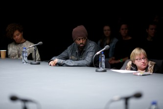 Three members of the audience at the table listen