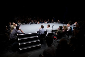 A long shot of a large group sat around in discussion around a large table