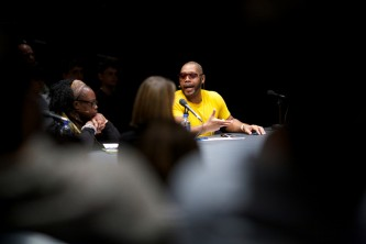 Michael Roberson Garcon gesticulates as they make a point at a table of people
