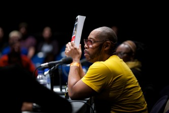 Michael Roberson Garcon holds a book up to show to the audience