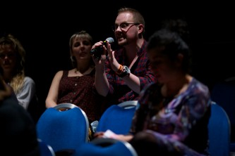 An audience member moves forward as they ask a question
