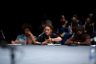 An audience member leans forward as they ask a question at the table