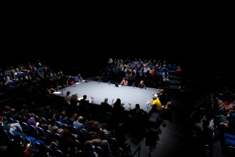 A long shot of the large table with folks round it and the audience on 4 sides