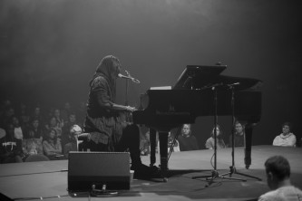 M Lamar dressed in a black cowl seated at a piano performs