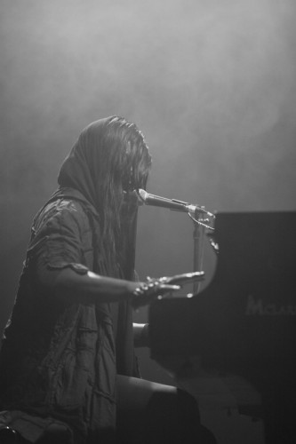 M Lamar sings though hair and hood whilst playing piano