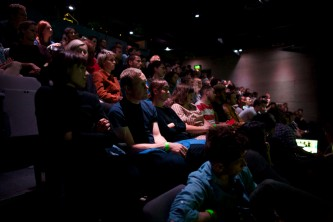 a side shot of the audience sat in rows watching a screen off shot