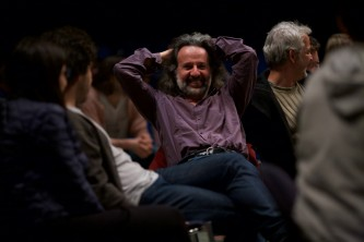 Peter Pal Pelbart hands behind his head smiles during the talk