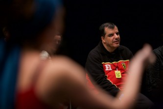 A member of Ueinzz in a black and red top listens to the discussion