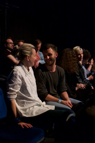 Two audience members smile at each other after one trys to cross the others leg